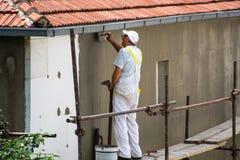 Almofariz de espalhamento do trabalhador sobre a isolação do isopor e malha com a pá de pedreiro na fachada da casa imagem de stock