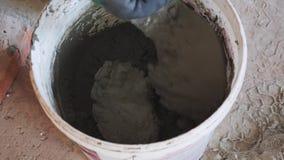 Almofariz de mistura da mão com uma pá de pedreiro no canteiro de obras Emplastro de mistura do trabalhador com a pá de pedreiro  filme
