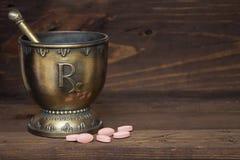 Almofariz e pilão de RX com as tabuletas cor-de-rosa no fundo de madeira Fotografia de Stock Royalty Free