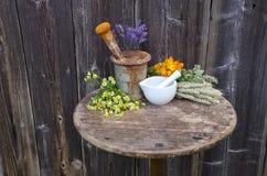 Almofarizes na tabela velha e em várias flores médicas do fitoterapia Imagem de Stock Royalty Free