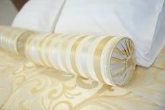 Almohada-amortiguador decorativo de la tela de oro en la cama primer fotografía de archivo libre de regalías