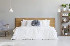 Almohada azul en la cama blanca con el cabecero de madera en interi del dormitorio foto de archivo