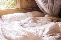 almohada blanca en cama y con la manta sucia de la arruga en Th del dormitorio Imágenes de archivo libres de regalías