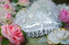 Almohada como corazón con los anillos de bodas Imágenes de archivo libres de regalías
