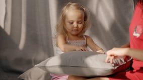 Almohada de perforación de la muchacha rubia feliz por los dedos meñiques, jugando con la mamá en cama almacen de video