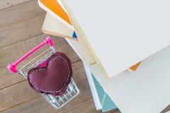 Almohada del corazón de Brown en el mini carro por la pila de libro en t de madera Foto de archivo