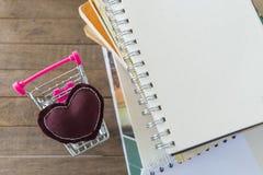 Almohada del corazón de Brown en el mini carro por la pila de libro en t de madera Fotografía de archivo libre de regalías