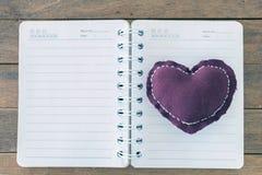 Almohada del corazón en un libro en blanco en la tabla de madera Fotografía de archivo libre de regalías