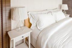 Almohada dos en dormitorio con la hoja y la lámpara blancas de cama Fotos de archivo