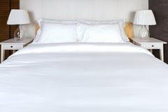 Almohada dos en dormitorio con la hoja y la lámpara blancas de cama Fotos de archivo libres de regalías