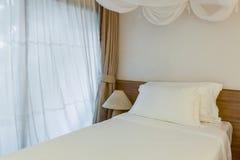 Almohada dos en dormitorio con la hoja y la lámpara blancas de cama Imagen de archivo libre de regalías