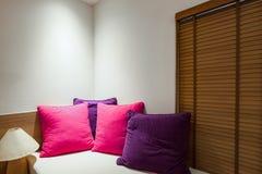 Almohada dos en dormitorio con la hoja y la lámpara blancas de cama Imágenes de archivo libres de regalías