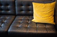 Almohada en el sofá de cuero negro imagen de archivo