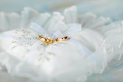 Almohada en forma de corazón con los anillos de oro de la boda Imágenes de archivo libres de regalías