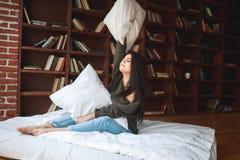 Almohada hermosa del abarcamiento de la mujer joven en cama por la mañana en Fotografía de archivo