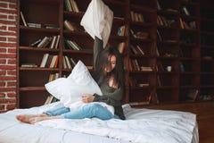 Almohada hermosa del abarcamiento de la mujer joven en cama por la mañana en Fotos de archivo