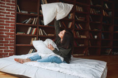 Almohada hermosa del abarcamiento de la mujer joven en cama por la mañana en Fotos de archivo libres de regalías