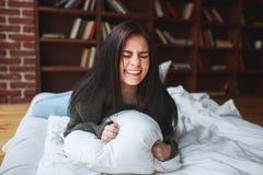 Almohada hermosa del abarcamiento de la mujer joven en cama por la mañana en Foto de archivo