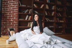 Almohada hermosa del abarcamiento de la mujer joven en cama por la mañana en Imagen de archivo