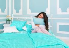 Almohada hermosa del abarcamiento de la mujer que se sienta joven en una cama Fotos de archivo libres de regalías