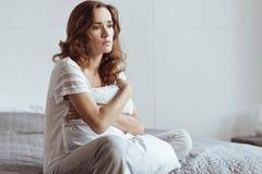 Almohada madura deprimida del abarcamiento de la mujer mientras que se sienta en cama Imagen de archivo libre de regalías