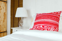 Almohada roja en dormitorio con la hoja y la lámpara blancas de cama Imagen de archivo libre de regalías