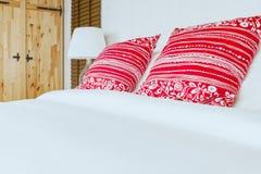 Almohada roja en dormitorio con la hoja y la lámpara blancas de cama Fotografía de archivo