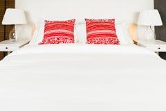 Almohada roja en dormitorio con la hoja y la lámpara blancas de cama Foto de archivo libre de regalías