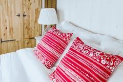 Almohada roja en dormitorio con la hoja y la lámpara blancas de cama Fotografía de archivo libre de regalías