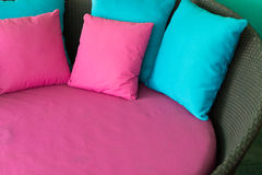 Almohada rosada y azul en el sofá marrón de la rota Fotos de archivo