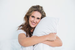 Almohada sonriente del abarcamiento de la mujer Fotografía de archivo libre de regalías