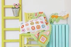 Almohada y manta hechas a mano en la silla Decoraciones caseras acogedoras Foto de archivo