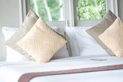 Almohadas, cama por la ventana en el dormitorio fotografía de archivo