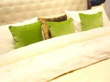 Almohadas coloridas en cama del hotel imagenes de archivo