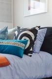 Almohadas coloridas en cama en dormitorio moderno Imagen de archivo libre de regalías