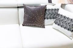 Almohadas de cuero en el sofá marrón imagen de archivo