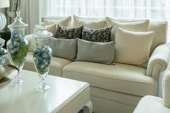 Almohadas decorativas blancas y grises en el sofá en la sala de estar Fotos de archivo