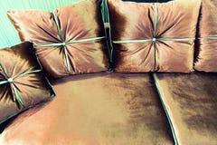 Almohadas del terciopelo en el sofá marrón imagen de archivo