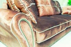 Almohadas del terciopelo en el sofá marrón Fotos de archivo