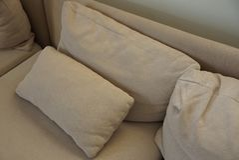 Almohadas marrones grises de la tela en el sofá imagenes de archivo