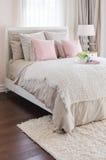 Almohadas rosadas en cama con la bandeja blanca de flor en casa Foto de archivo