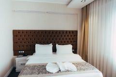 Almohadas suaves c?modas en la cama Hojas y almohada blancas del lecho del primer en fondo ligero del sitio de la pared Concepto  imagen de archivo libre de regalías