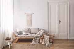 Almohadas y manta en el sofá de madera en el interior blanco del desván con la puerta y la tabla en la alfombra Foto verdadera foto de archivo