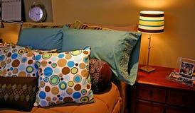Almohadillas coloridas en cama Imagenes de archivo