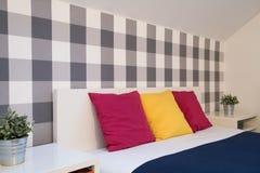 Almohadillas coloridas en cama Foto de archivo