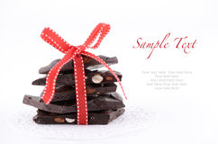 Almond bark. Dark chocolate almond bark in a stack with red ribbon on white background Royalty Free Stock Image