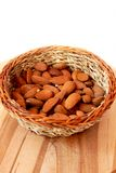 Almond basket. Braided basket with almond placed on a wood royalty free stock image