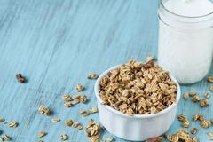 Almond Breakfast Cereal Granola With Glass of Milk Close Up. Almond breakfast granola in white bowl on blue background with glass of milk close up royalty free stock photo