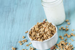 Almond Breakfast Cereal Granola With Glass of Milk. Almond breakfast granola in white bowl on blue background with glass of milk close up stock image