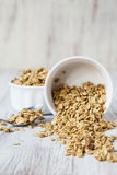 Almond Breakfast Cereal Granola Spilling From White Bowl. Healthy Almond breakfast granola spilling from white bowl with spoon royalty free stock images